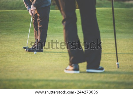 Golf green sceen - golfer putting near the hole, short putt (colort toned image with reduced contrast and some added noise) - stock photo