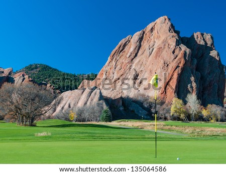 Golf green with flagstick and ball with a dramatic rocky background and blue sky - stock photo