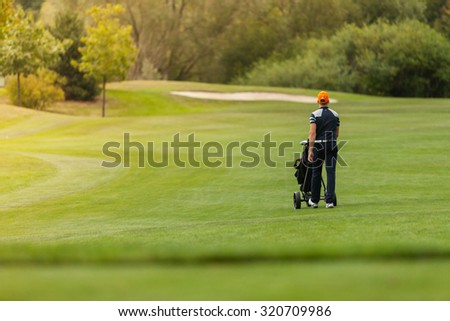 Golf man player holding trolley with clubs - stock photo