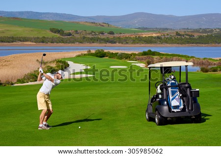 golf man playing shot with cart nearby on vacation - stock photo