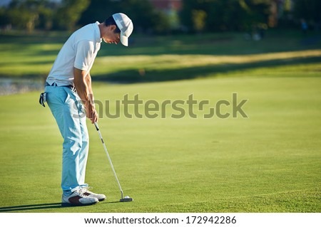 Golf man putting on green for birdie while on vacation - stock photo