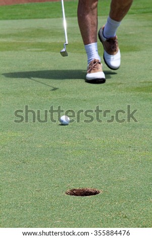 Golf man putting on green for birdie while on vacation. Feet walking towards ball. Focus on hole. - stock photo