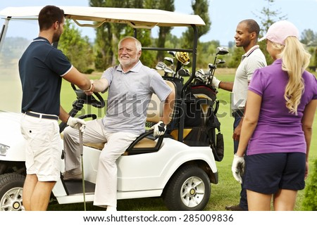 Golf partners greeting on the fairway around golf cart. - stock photo