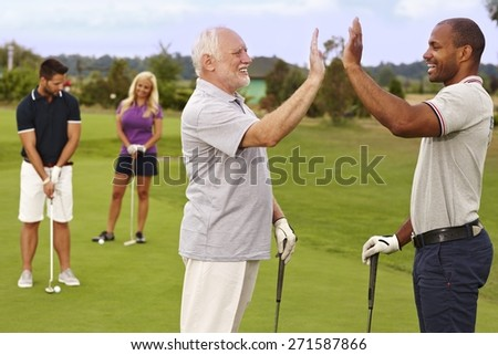 Golf partners happy for good shot on the green. - stock photo