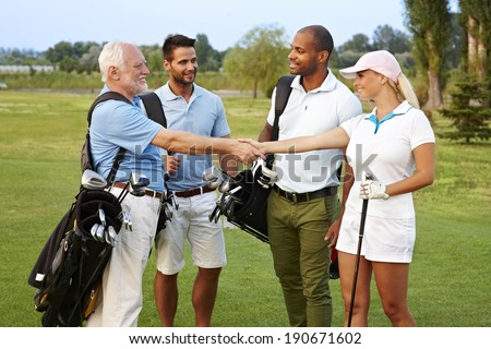 Golf partners shaking hands on the fields, smiling happy. - stock photo