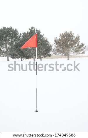 Golf Pin Red Flag Blowing in the Wind and Snow - stock photo