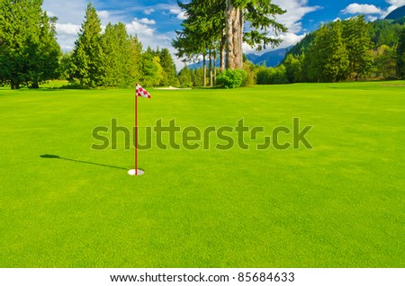 Golf place with gorgeous green and fantastic mountain and blue sky view - stock photo