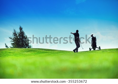 Golf player at a golf course with a wheel bag - stock photo