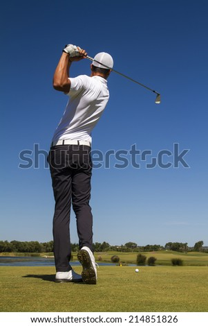 Golf player hitting a golf ball in a beautiful golf course. - stock photo