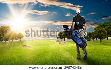 Golf Player in a black shirt walking with a bag of golf clubs on his back, on a golf course. - stock photo