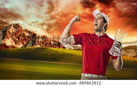 Golf Player in a red shirt celebrating with a glass trophy in his hands, on a golf course.