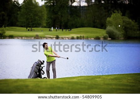 Golf player pitching golf ball at lake with ball in the air. - stock photo