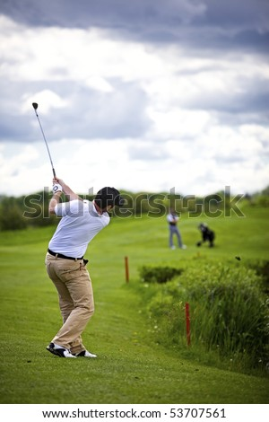 Golf player pitching golf ball over divot with second player in the background watching him. - stock photo