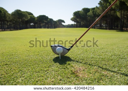 golf player placing ball on tee. beautiful sunrise on golf course landscape  in background - stock photo