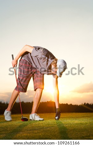 Golf player preparing a golf ball while sunset - stock photo