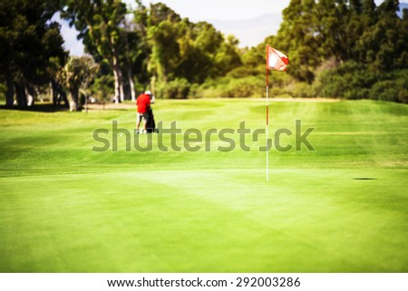 Golf player preparing approach shot to last hole of the course. - stock photo