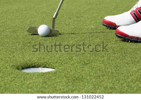 Golf player putting ball into hole - stock photo