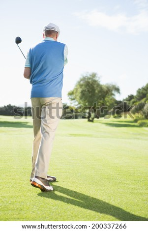 Golf player taking a shot on a sunny day at the golf course - stock photo