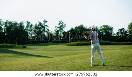 Golf player teeing off. Man hitting golf ball from tee box with driver isolated on sunny green golf course. - stock photo