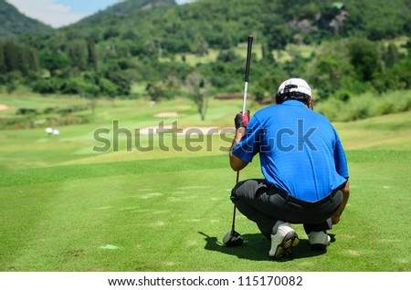 golf player with putter squatting to analyze the green at golf c