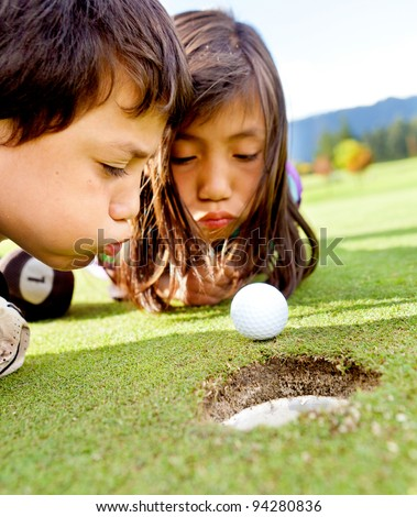 Golf players cheating blowing to get the ball into the hole - stock photo