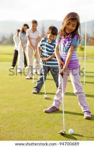 Golf players practicing to hit the ball - stock photo