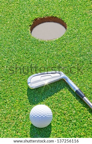 Golf putter ball near the hole in the vertical format. Against the background of grass. - stock photo