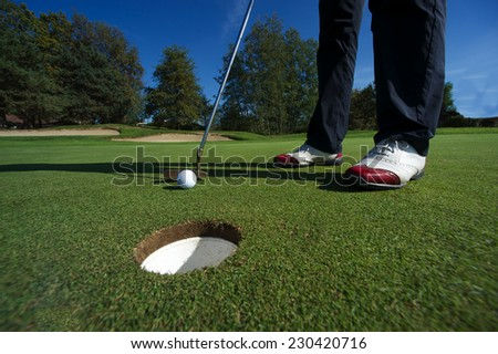 Golf putting and red shoes - stock photo