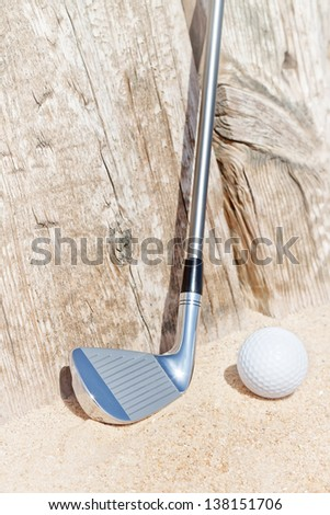 Golf stick and ball on the sand. Close-up. - stock photo