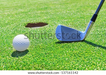 Golf stick  ball near the hole. Against the background of grass. - stock photo