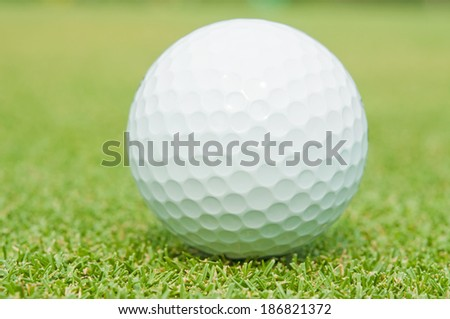 Golfball on grass infront of the green - stock photo