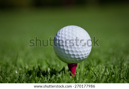Golfball on red wooden tee - stock photo
