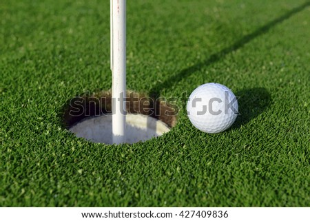 Golfball with Flagstick and hole on putting green on golf course