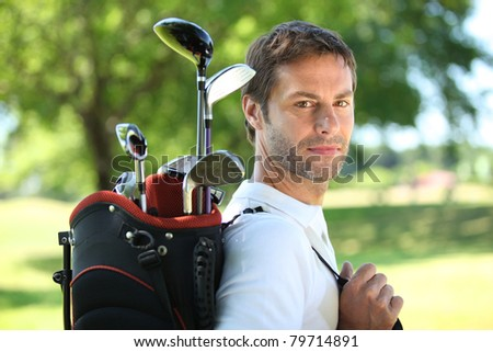 Golfer carrying clubs