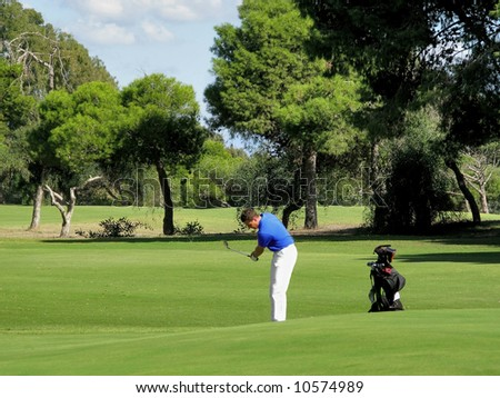 Golfer chipping onto the green on a beautiful sunny day. - stock photo