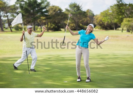 Golfer couple celebrating success while standing on field - stock photo
