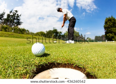 Golfer drove the ball into the hole on putting green; summer sunny day, selective focus on ball - stock photo