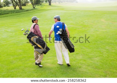 Golfer friends walking and chatting on a sunny day at the golf course - stock photo