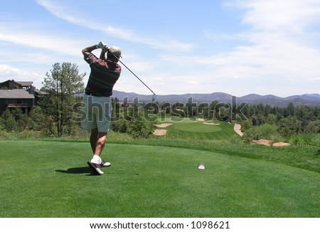 Golfer hitting golf ball off tee box on beautiful golf course - stock photo