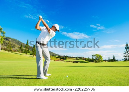Golfer Hitting Golf Shot with Club on the Course  - stock photo