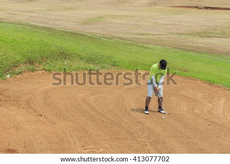 Golfer in a green shirt blasting out of bunker onto green. - stock photo