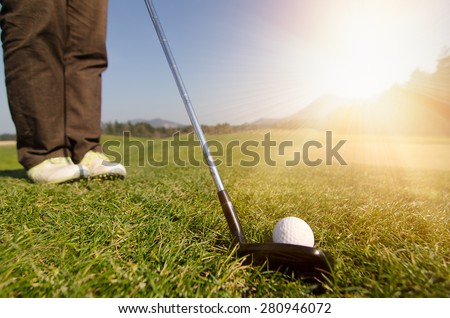 Golfer is chipping a golf ball onto the green with driver golf club. Legs and feet in the background. Green grass with forest and mountains in the background. Soft focus or shallow depth of field. - stock photo