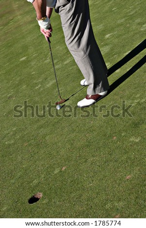 Golfer is hitting the golf ball to the hole