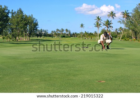 Golfer kneels while setting golf ball on course for alignment with hole