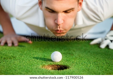 golfer lying on grass and blowing in the ball,  just need to give it a little help. - stock photo
