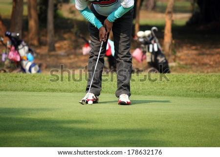 Golfer making the perfect putt on the green  - stock photo