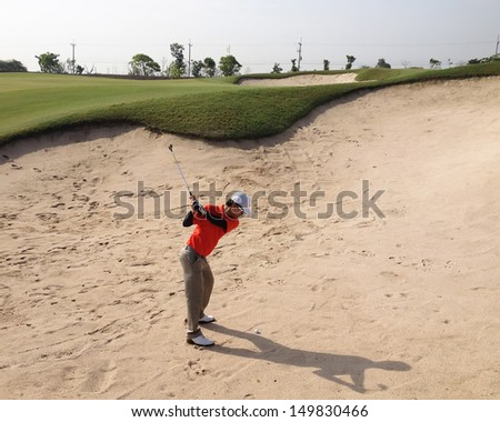 Golfer on the sand trap - stock photo