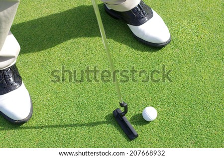 Golfer on training putt golf ball - stock photo