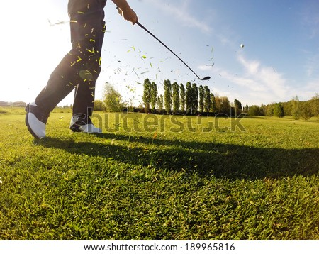 Golfer performs a golf shot from the fairway. - stock photo
