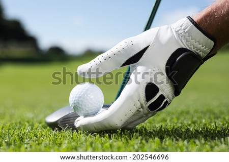 Golfer placing golf ball on tee on a sunny day at the golf course - stock photo